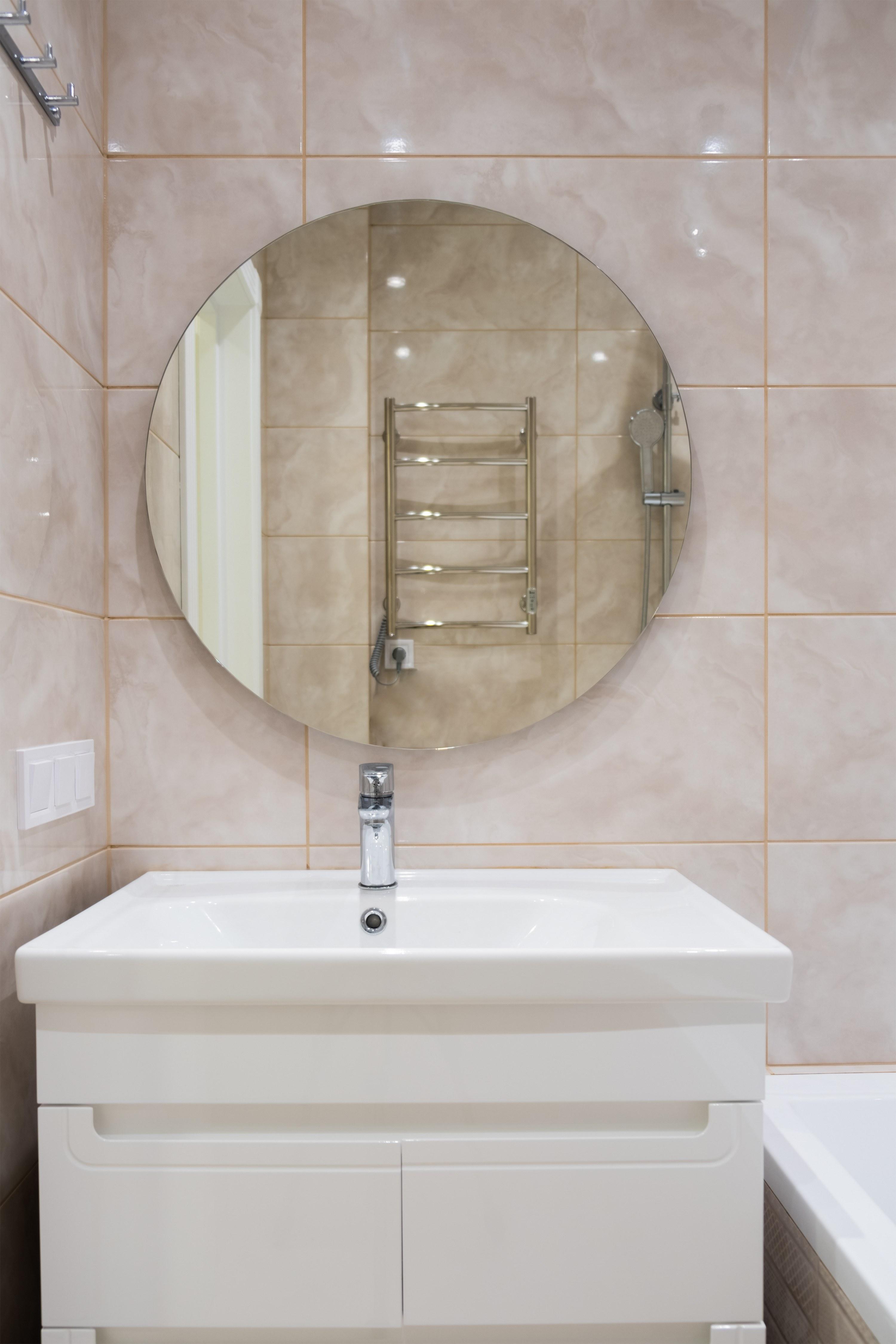 Умывальник с зеркалом в ванной после ремонта